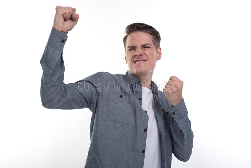 Yeah! Handsome young man; isolated on white background with a winner gesture royalty free stock photo