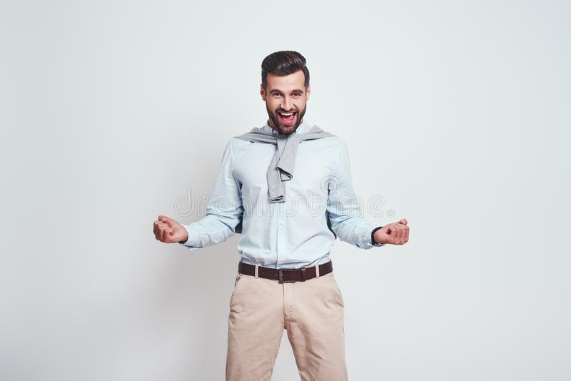 Yeah, i did it. Happy smiling man with beard is celebrating a success, keeping hands clenched in fists while standing on stock image