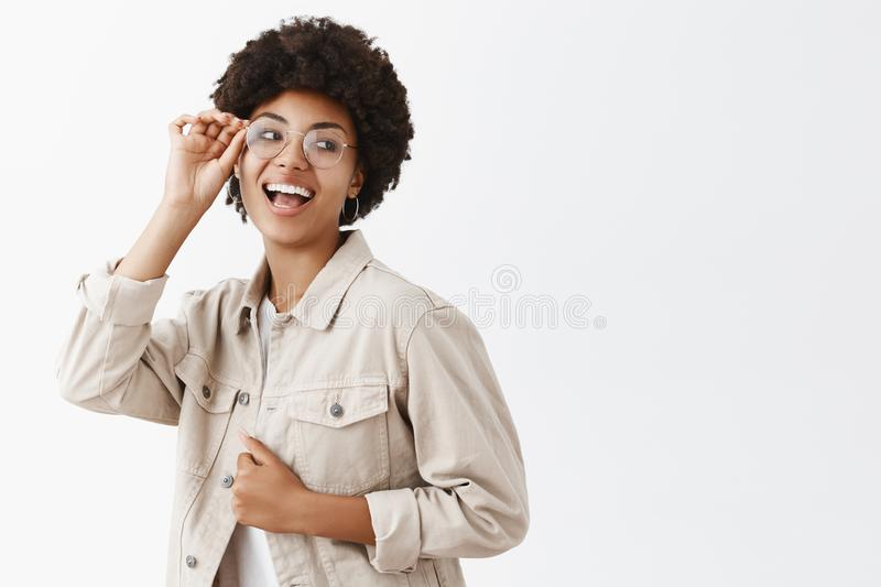 Yeah let us enjoy life. Stylish carefree and confident female dark-skinned blogger in glasses and beige shirt, touching royalty free stock photos