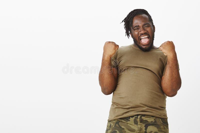 Yeah nós fizemo-lo Retrato do indivíduo gordo de pele escura feliz energético no t-shirt militar, levantando as mãos com apertado imagem de stock royalty free
