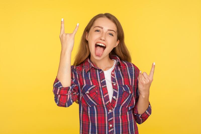 Yeah, that`s crazy and awesome! Portrait of overjoyed excited ginger girl sticking out tongue and showing rock and roll hand. Yeah, that`s crazy and awesome! royalty free stock photography