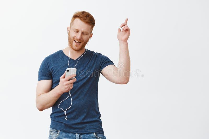 Yeah stort ljud i ny hörlurar Studioskott av den stiliga bekymmerslösa och glade moderna skäggiga mannen i blå t-skjorta arkivfoton