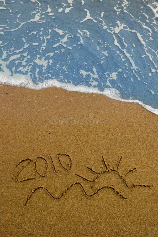 Year 2010 written on sand stock photos