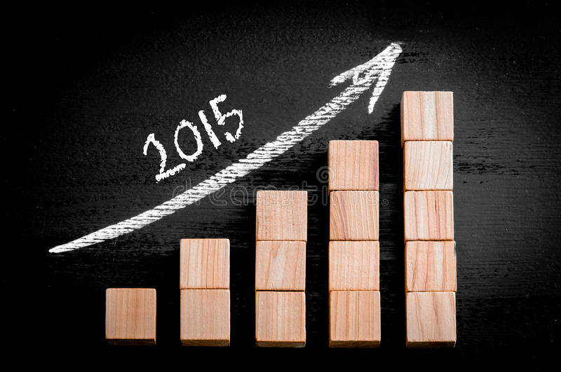 Year 2015 on ascending arrow above bar graph. Of Wooden small cubes isolated on black background. Chalk drawing on blackboard. Business Concept image stock images
