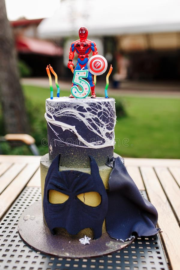 5 year baby birthday cake with spiderman on top and batman mask on table outdoor royalty free stock photos