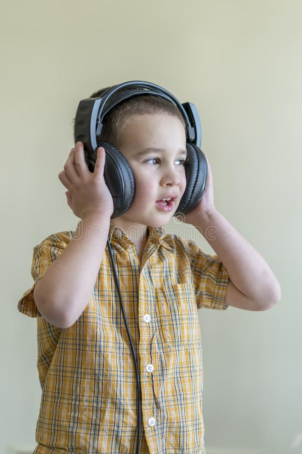 A 4 year boy in a shirt attentively listens to music in big black headphones. Little boy listening to music in big black headphone stock photos