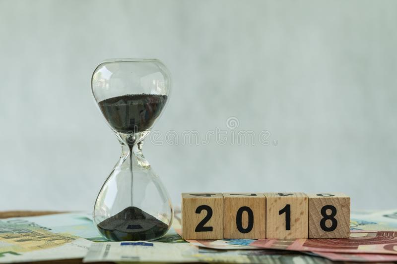 Year 2018 business time countdown or long term investment concept as hourglass or sandglass on pile of Euro banknotes with wooden. Cube block number 2018 stock images