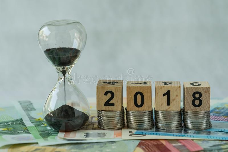 Year 2018 business time countdown or long term investment concept as hourglass or sandglass on pile of Euro banknotes with wooden royalty free stock images