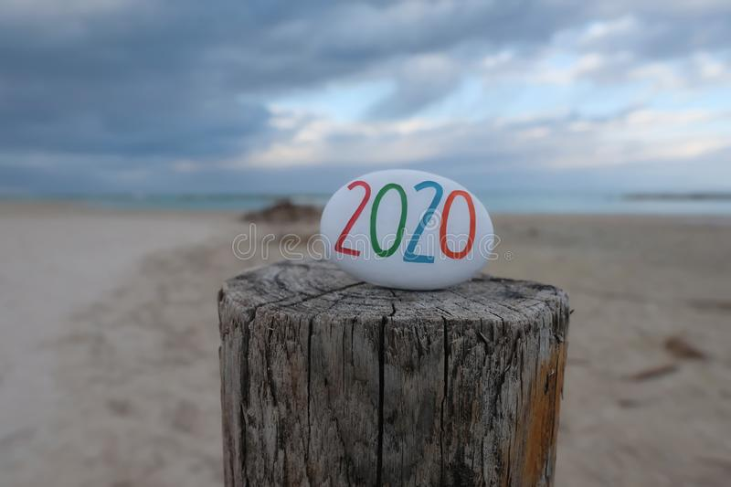 Year 2020 carved and colored on a stone over a wooden pole for a unique happy new year message royalty free stock images