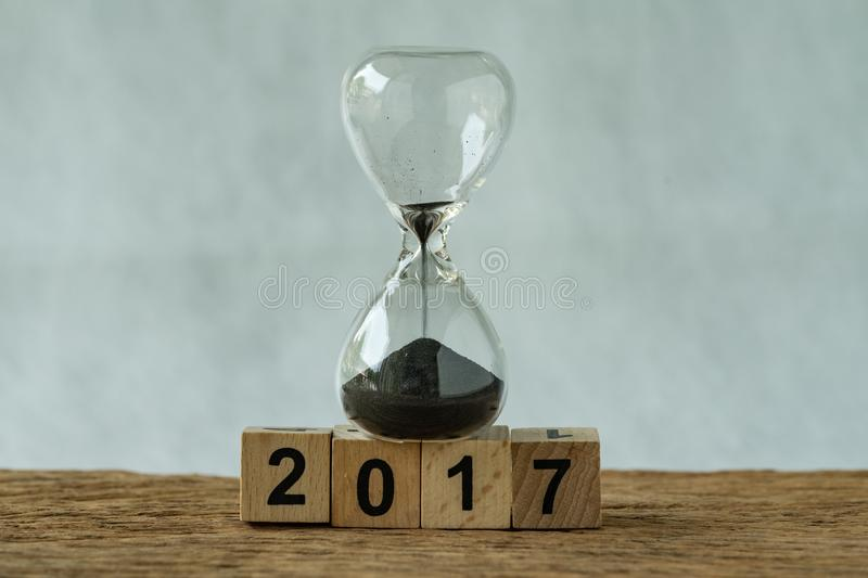 Year end 2017 business time countdown or improvement review concept as hourglass or sandglass with wooden cube block number 2017 royalty free stock photos
