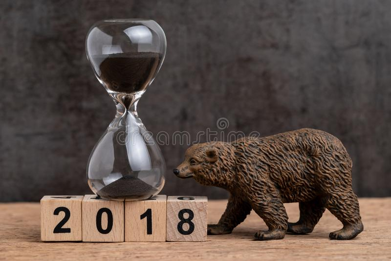 Year end count down for 2018 financial or bear market concept with sandglass or hourglass and bear figure waking on cube block stock photo