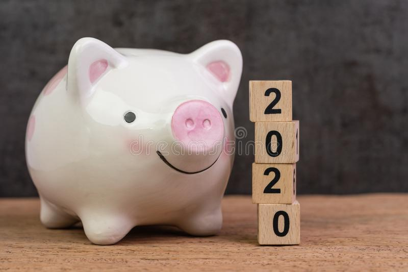 Year 2020 financial goal, savings, budget or investment, happy smiling pink piggy bank with stack of wooden cube blocks with. Number 2020 on table and dark stock image