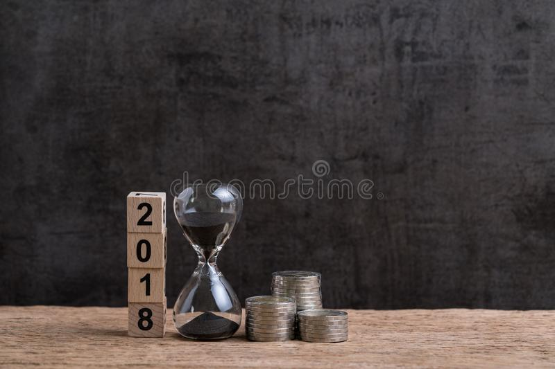Year 2018 financial or investment time or goals concept with hourglass or sandglass and stack of coins and cube block with number stock image