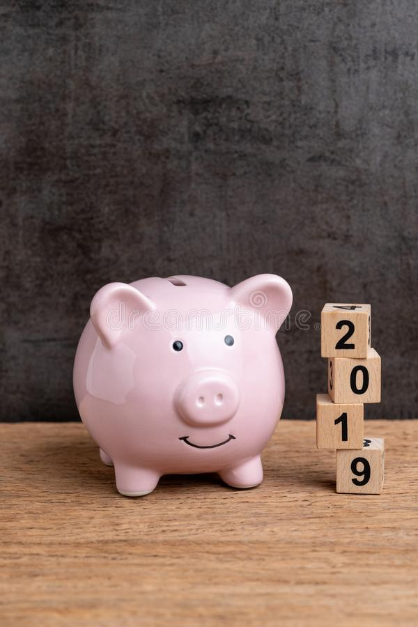 Year 2019 financial target, budget, investment or business goals concept, pink piggy bank and stack of cube wooden block building. Year number 2019 on wood royalty free stock images
