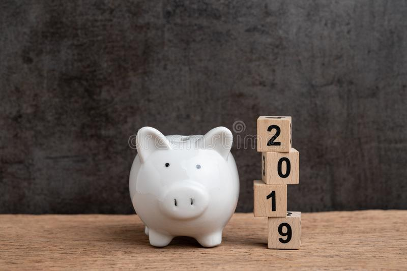 Year 2019 financial target, budget, investment or business goals concept, white piggy bank and stack of cube wooden block building. Year number 2019 on wood royalty free stock image