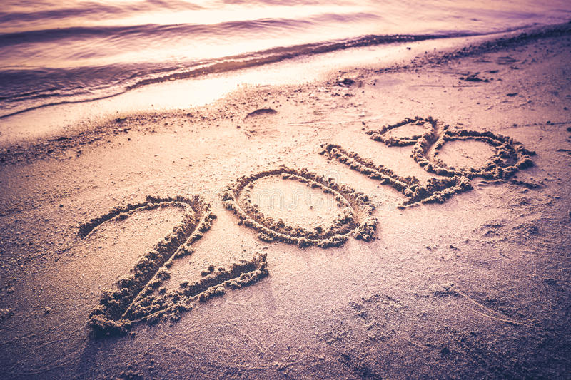 Year 2018 handwritten on seashore sand. Vintage tone. Year 2018 handwritten on seashore sand with sea wave water. Concept of upcoming new year and passing of royalty free stock photo