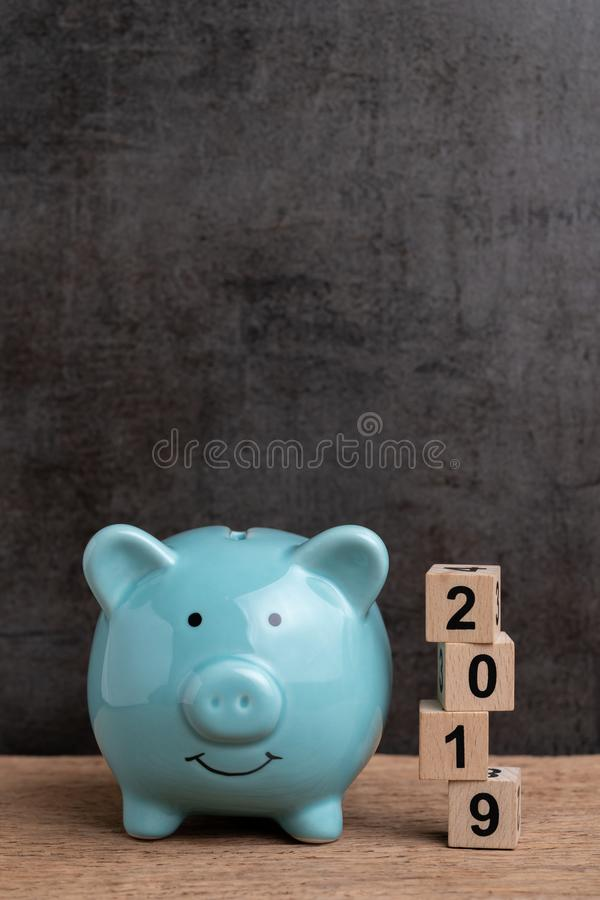 Year 2019 happy saving target, budget, investment or finance goals concept, blue piggy bank and stack of cube wooden block. Building unstable risk year number stock image