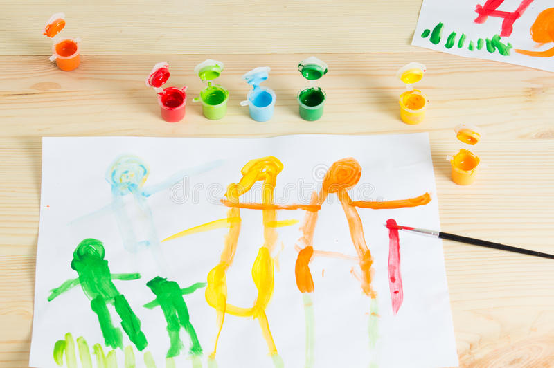 3 year kids drawing happy family picture on the wooden table. To stock image