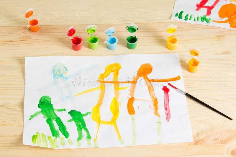 3 year kids drawing happy family picture on the wooden table. To stock images