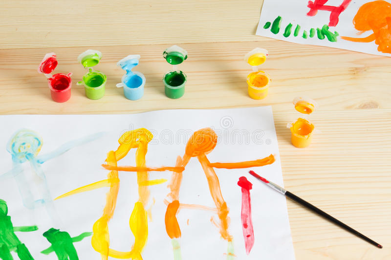 3 year kids drawing happy family picture on the wooden table. To royalty free stock photo