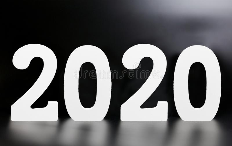 Year 2020 made from wooden white numbers on a black background stock photo