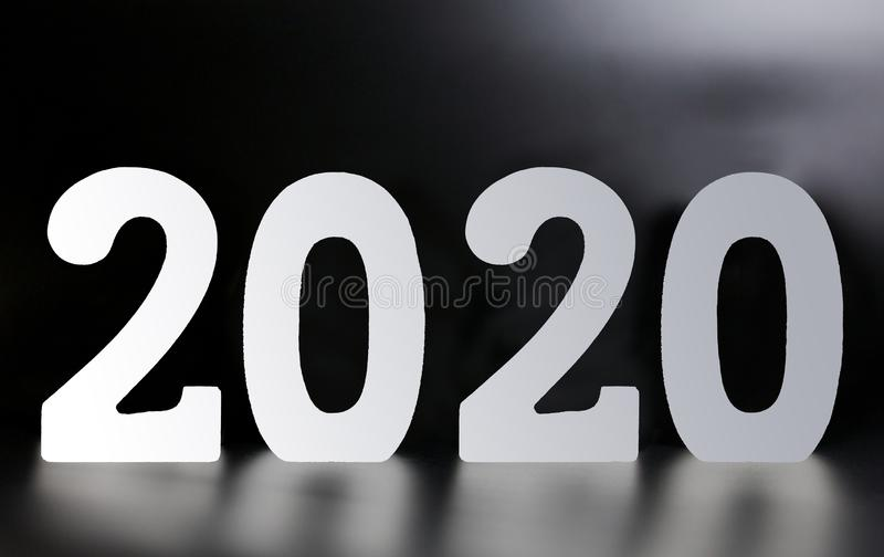 Year 2020 made from wooden white numbers on a black background royalty free stock image