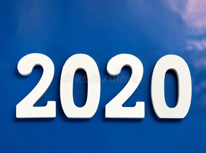 Year 2020 made from wooden white numbers on a blue background royalty free stock images