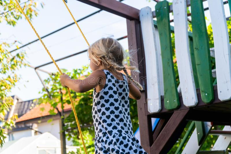 3-5 year old blond girl having fun on a swing outdoor. Summer playground. Girl swinging high. Young child on swing in royalty free stock photo