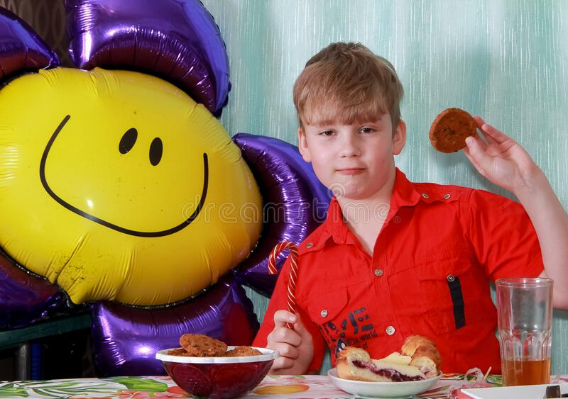 A 10-year-old boy eating a sweet berry pie.On a blue - blue background, close-up. Boy, young, child, desserts, candy, cookies, hap royalty free stock photos