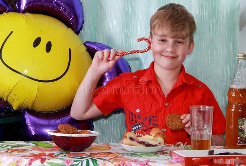 A 10-year-old boy eating a sweet berry pie.On a blue - blue background, close-up. Boy, young, child, desserts, candy, cookies, hap royalty free stock image
