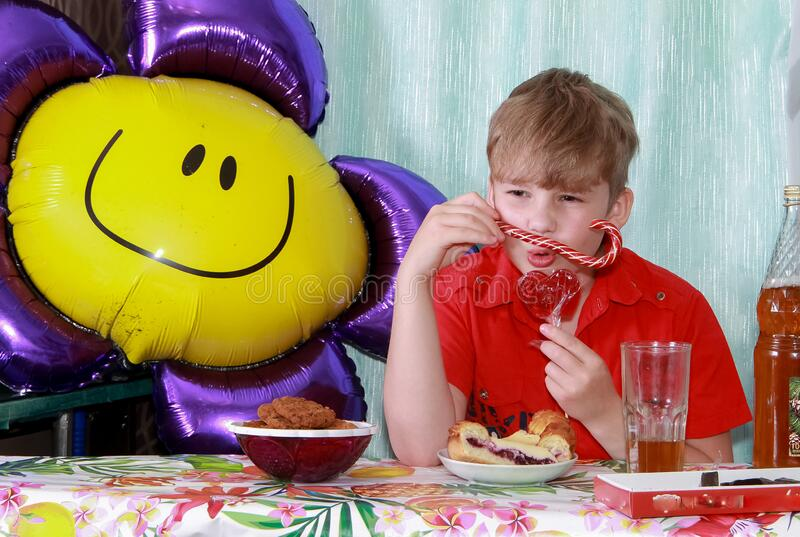 A 10-year-old boy eating a sweet berry pie.On a blue - blue background, close-up. Boy, young, child, desserts, candy, cookies, hap stock images