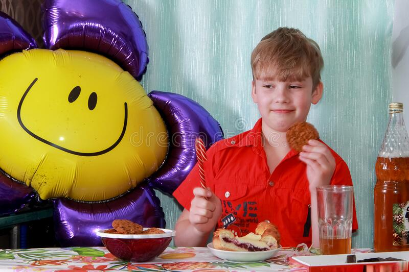 A 10-year-old boy eating a sweet berry pie.On a blue - blue background, close-up. Boy, young, child, desserts, candy, cookies, hap royalty free stock images