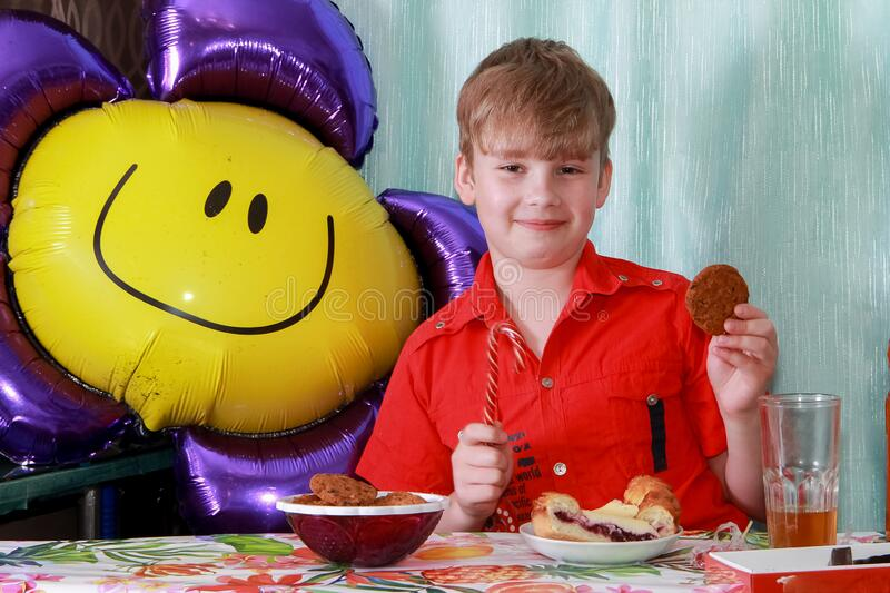 A 10-year-old boy eating a sweet berry pie.On a blue - blue background, close-up. Boy, young, child, desserts, candy, cookies, hap stock photography