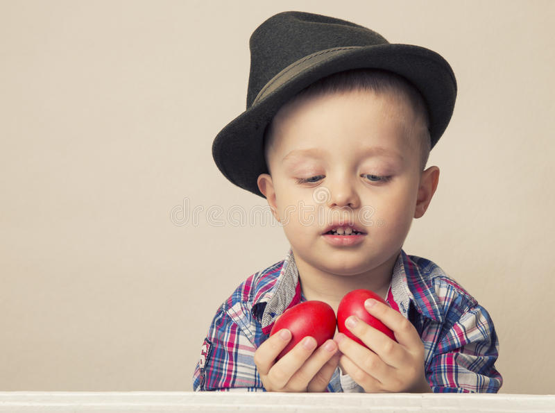 4 year old boy in a hat and shirt holding hands red Easter eggs, looks at eggs stock image
