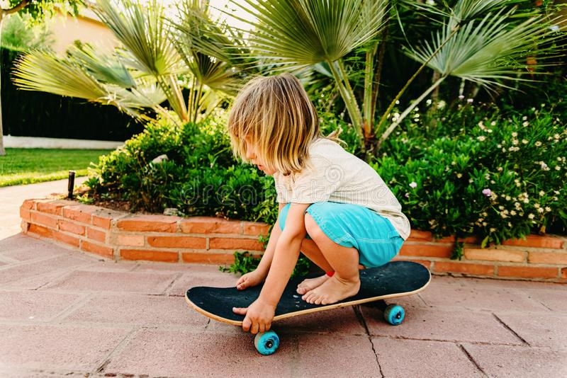 5 year old boy practicing skate in his back yard afraid of falling stock photo