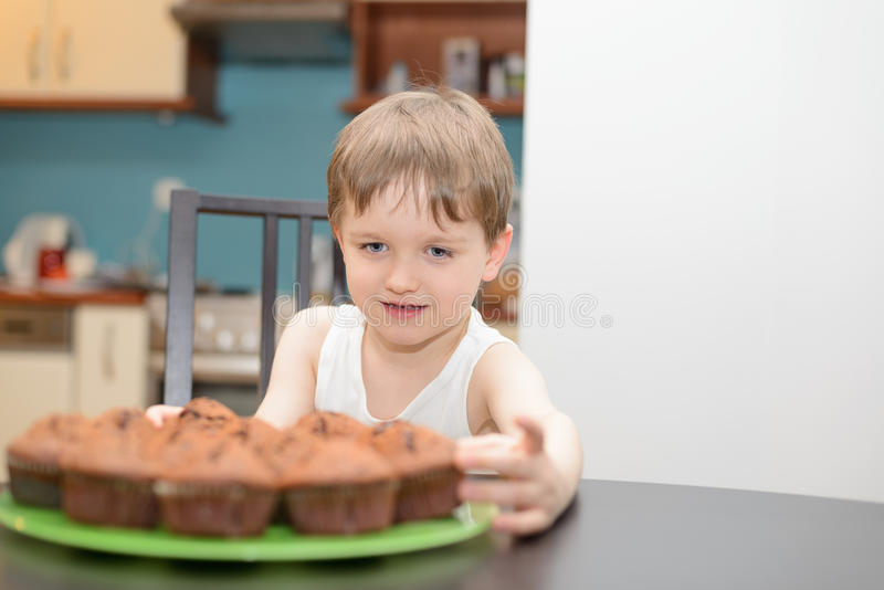 4 year old boy reaching for a chocolate cake stock photography