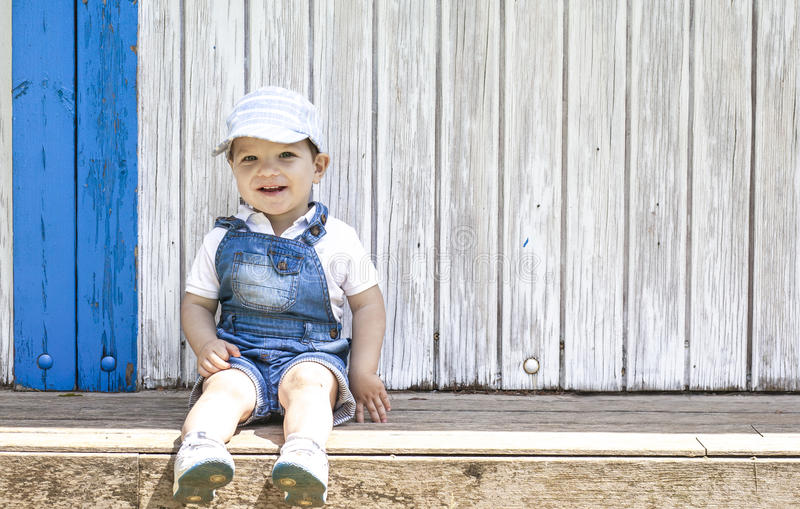 2 year-old boy sitting portrait at wooden beach hut. He wears a cap royalty free stock photography