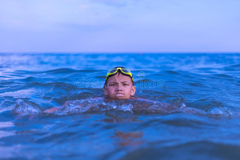 A 10-year-old boy swims in the sea at dawn with glasses for swimming. Child, happy, smiling, people, smile, attractive, happiness, kid, person, adult royalty free stock photos