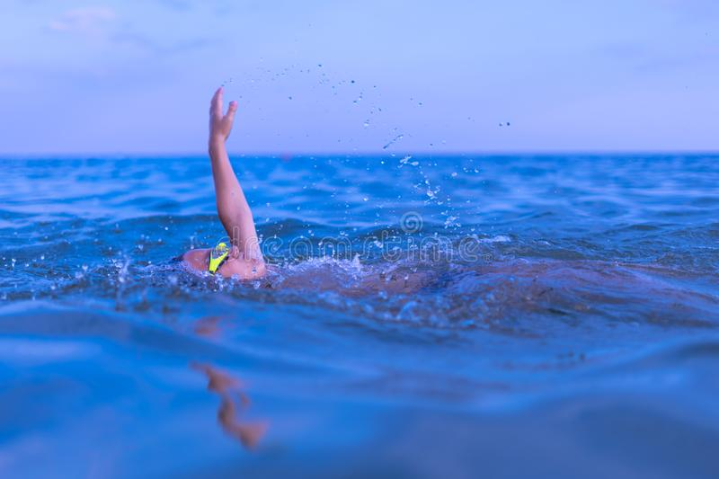 A 10-year-old boy swims in the sea at dawn with glasses for swimming. Child, happy, smiling, people, smile, attractive, happiness, kid, person, adult stock photo
