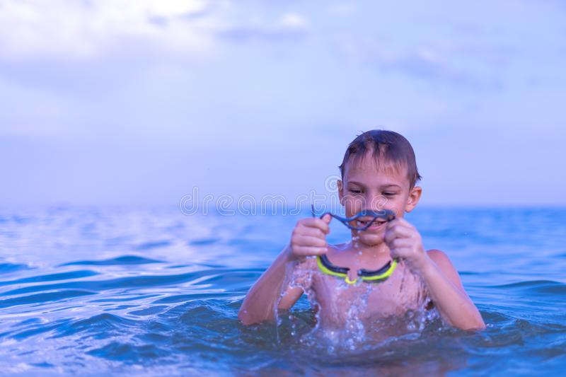 A 10-year-old boy swims in the sea at dawn with glasses for swimming. Child, happy, smiling, people, smile, attractive, happiness, kid, person, adult stock photography