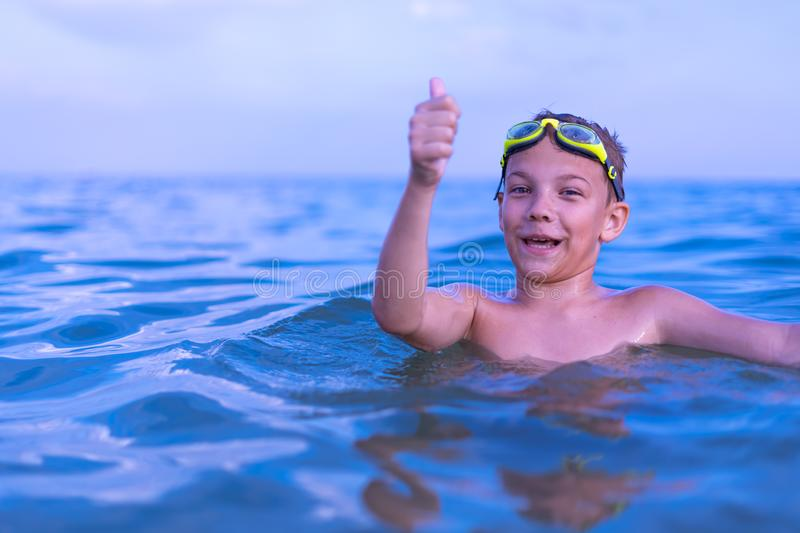 A 10-year-old boy swims in the sea at dawn with glasses for swimming. Child, happy, smiling, people, smile, attractive, happiness, kid, person, adult stock image
