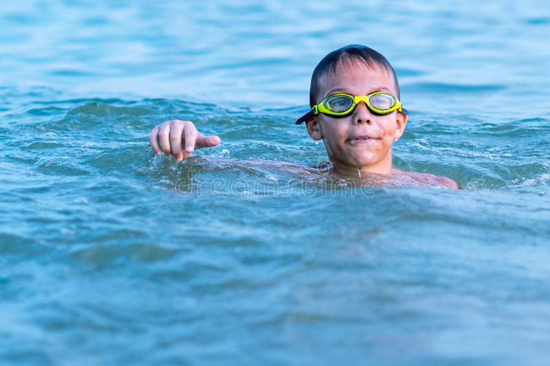 A 10-year-old boy swims in the sea at dawn with glasses for swimming. Child, happy, smiling, people, smile, attractive, happiness, kid, person, adult royalty free stock images