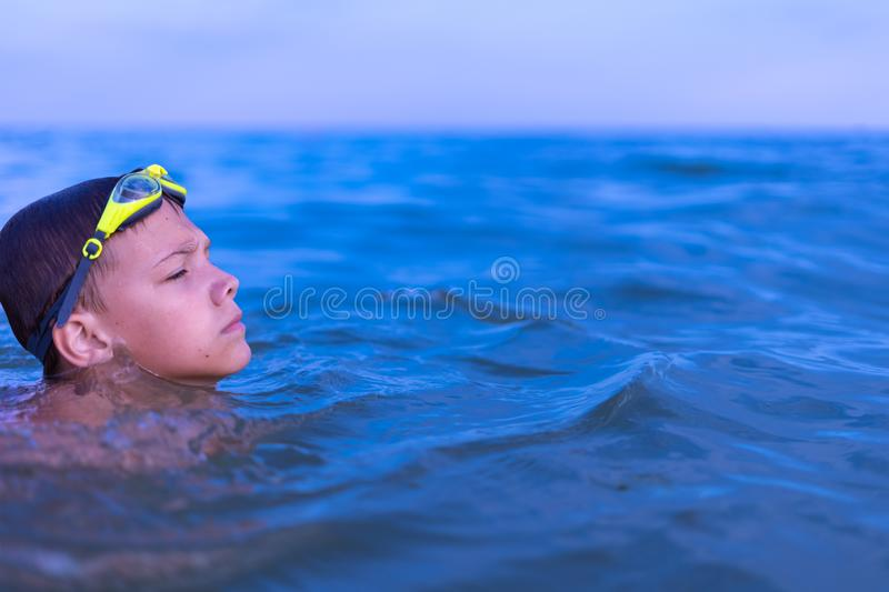 A 10-year-old boy swims in the sea at dawn with glasses for swimming. Child, happy, smiling, people, smile, attractive, happiness, kid, person, adult royalty free stock image