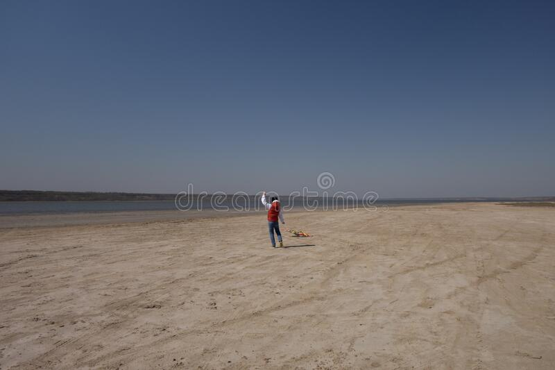 A 10 year old boy in a white sweatshirt and orange vest launches a kite on a deserted beach in solitude royalty free stock photography