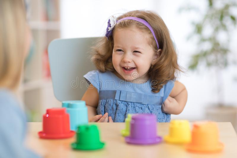 2 year old child playing with educational cup toys at home. stock image