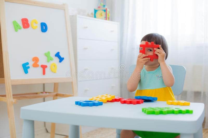Preschool child 3 years playing with colorful toy blocks. A 3 year old child plays at a table with colorful toy blocks. Children play with educational toys in royalty free stock photos