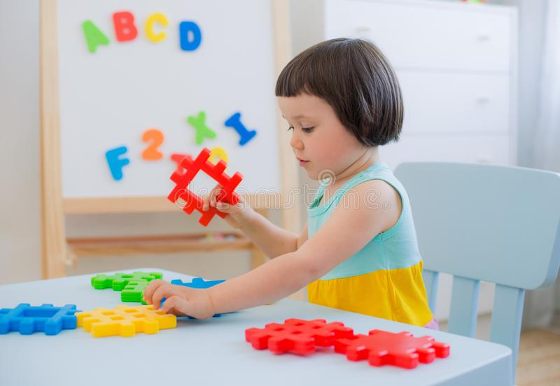 Preschool child 3 years playing with colorful toy blocks. A 3 year old child plays at a table with colorful toy blocks. Children play with educational toys in royalty free stock photography