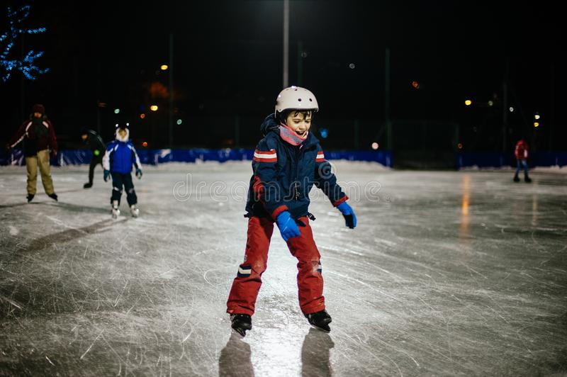 10 year old childl skates on the ice in the evening on an illuminated track royalty free stock photo