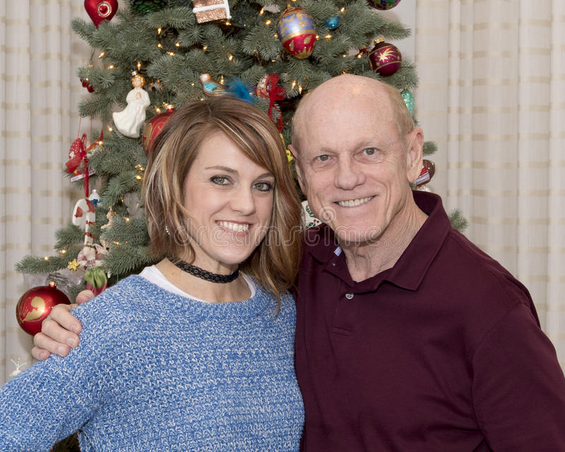 69-year old father and beautiful 43-year old daughter standing in front of a Christmas tree royalty free stock photo