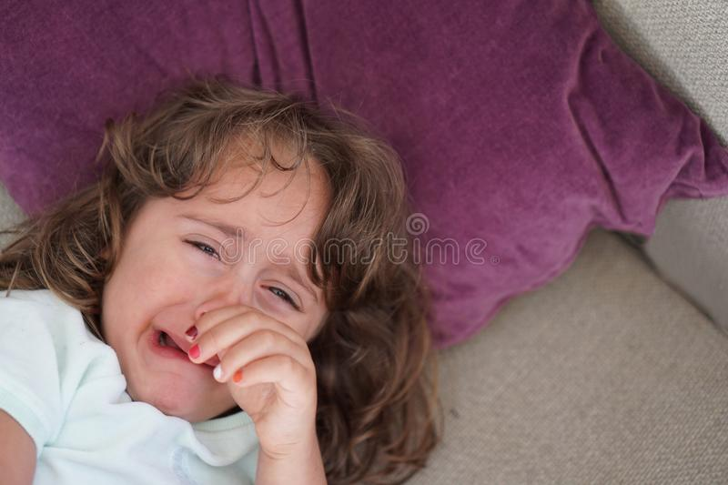 A 4-year-old girl cries after she has been scolded by her parents. A 4-year-old girl cries desperately after she has been scolded by her parents, hysteria royalty free stock images
